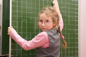 The schoolgirl washes a blackboard with a rag in a classroom
